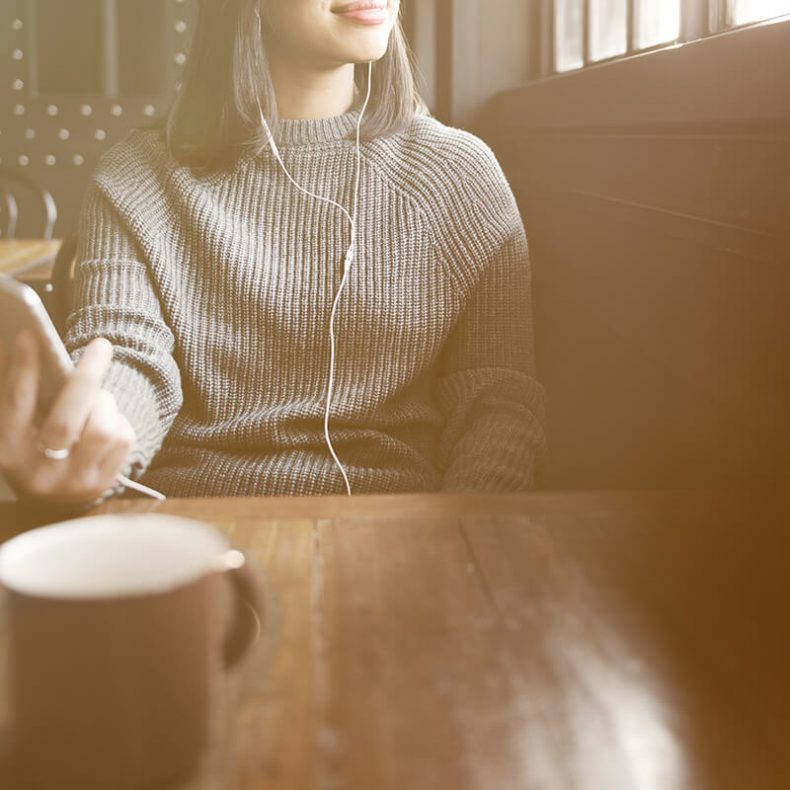 Woman drinking coffee at cafe using earphones